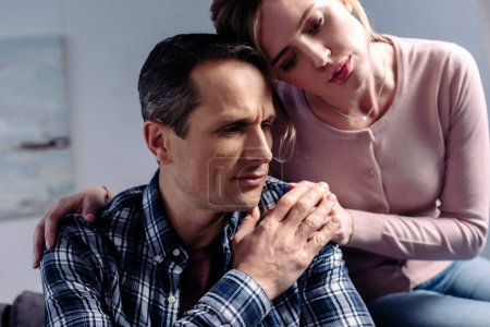 Photo for Portrait of woman hugging sad man that sitting on sofa at home - Royalty Free Image