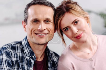 portrait of smiling couple in love looking at camera at home