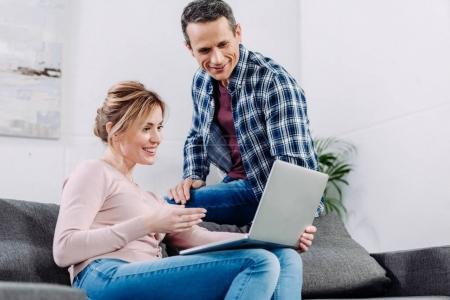Photo pour Couple souriant en utilisant un ordinateur portable sur le canapé à la maison - image libre de droit