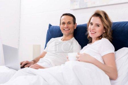 Photo pour Portrait d'un couple gai avec ordinateur portable dans le lit à la maison - image libre de droit