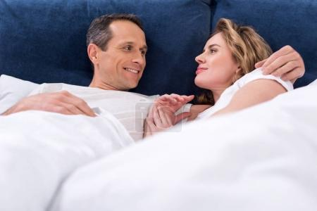 portrait of couple in love resting in bed together at home