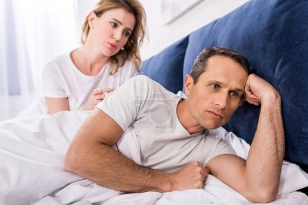 portrait of upset man lying in bed with wife behind