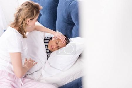 woman checking temperature of ill husband in bed at home