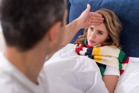 Photo pour Homme vérifier la température de la femme malade au lit - image libre de droit