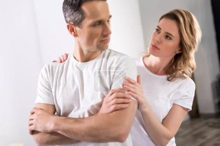 portrait of wife hugging upset husband at home