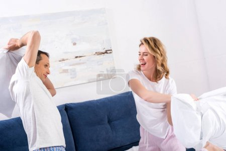 Photo for Happy couple having pillow fight in bedroom at home - Royalty Free Image