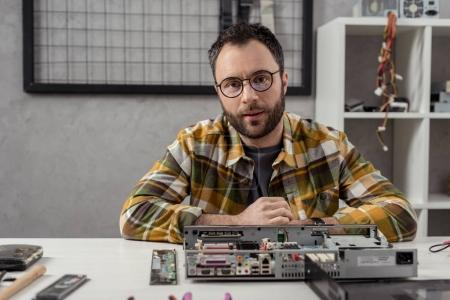 man looking at camera against broken computer on table