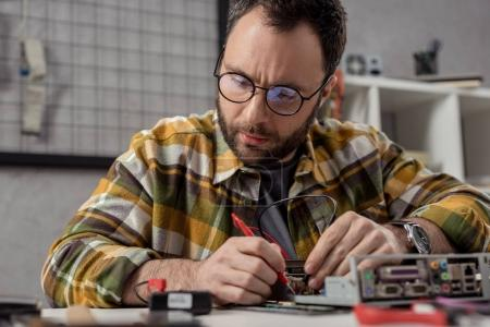 man using multimeter while fixing broken computer