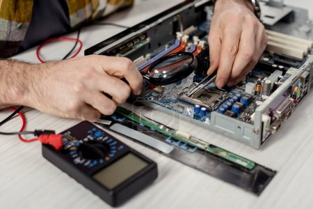 Photo for Cropped image of hands fixing motherboard of pcwith multimeter - Royalty Free Image