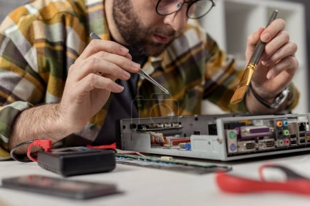 Photo for Man using multimeter and whisk while fixing computer motherboard - Royalty Free Image