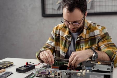 Photo pour Réparateur en utilisant le multimètre tout en fixant l'ordinateur cassé et en regardant vers le bas - image libre de droit