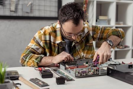 Photo for Repairman using tongs while fixing broken pc - Royalty Free Image