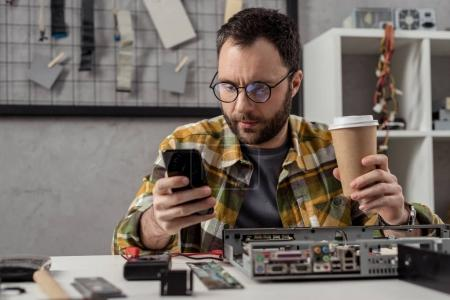 repairman using smartphone while holding coffee in hand