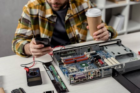 cropped image of man with coffee in hand using smartphone over broken pc