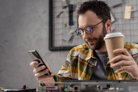 man with coffee in hand using smartphone over broken pc