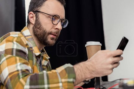 man in eyeglasses with coffee to go using smartphone