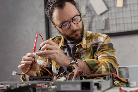 man using multimeter while fixing pc and looking away