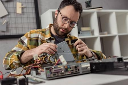 repairman sitting against table and fixing pc