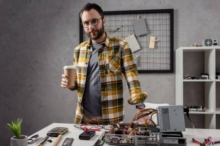man with coffee in hands standing against table with computer parts