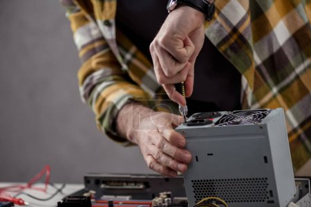 cropped image of man with screwdriver fixing computer part