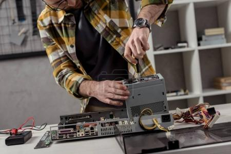Photo for Man with screwdriver fixing pc on table - Royalty Free Image