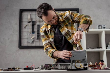 man adjusting details while fixing computer on table