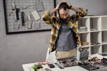 tired repairman looking down on broken computer