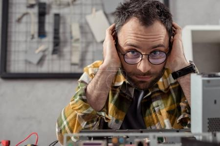tired repairman siitng against broken pc and looking at camera