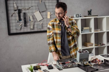 repairman with hand on cheek looking away over broken computer on table