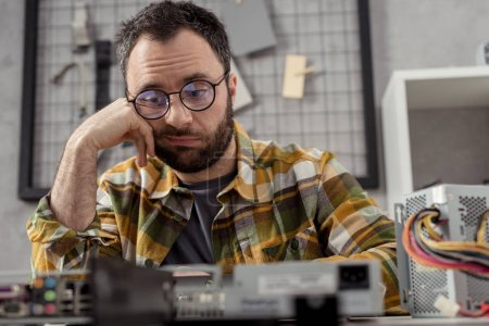 Photo for Discouraged repairman looking at broken pc - Royalty Free Image