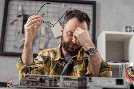 tired man holding glasses in hand with eyes closed against broken computer