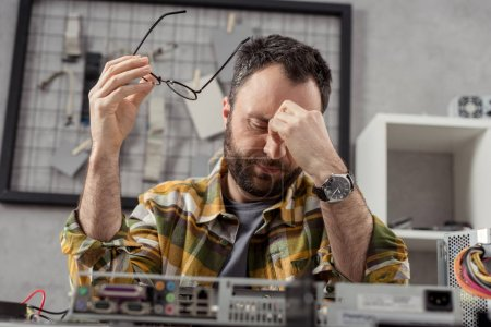 Photo for Tired man holding glasses in hand with eyes closed against broken computer - Royalty Free Image