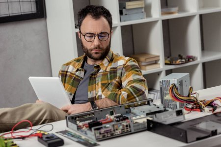 man using digital tablet while sitting against broken pc on table