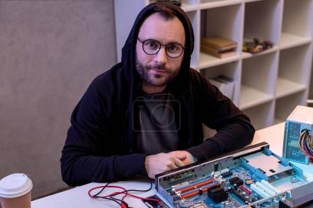 man in hoodie sitting against broken computer on table