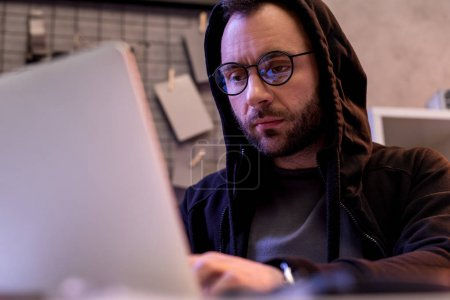 man in glasses using laptop while sitting