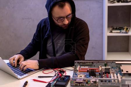 Photo for Man in hoodie using laptop while looking on broken pc - Royalty Free Image