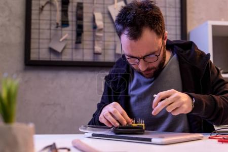 man choosing attachments to screwdriver over digital tablet