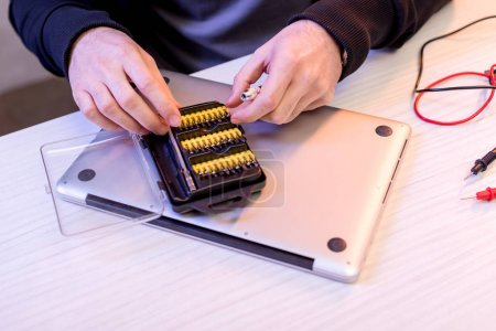 cropped image of hands and attachments to screwdriver over digital tablet