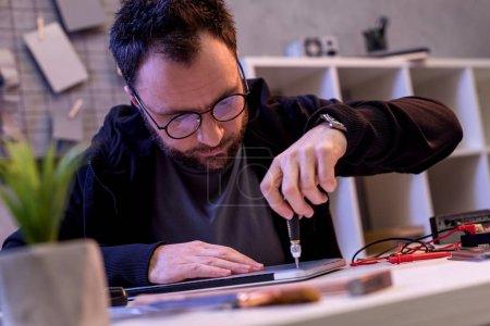 caucasian man with screwdriver fixing digital tablet