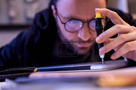 man using screwdriver while fixing  digital tablet