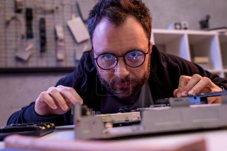 man in glasses looking on broken detail on table