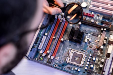 cropped image of man using magnifier while fixing motherboard