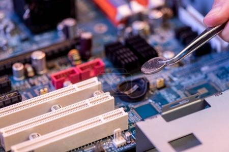 Photo pour Image recadrée de la main et pinces avec batterie à la carte mère - image libre de droit