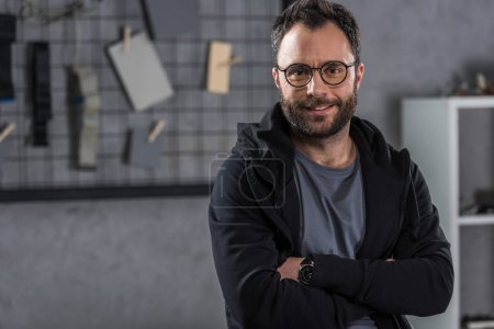 smiling man with glasses  looking at camera with arms crossed