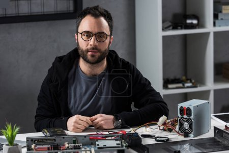man sitting against broken computer on table and looking at camera
