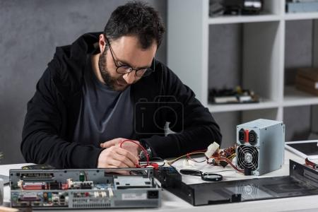 Photo for Man using multimeter while fixing broken pc - Royalty Free Image