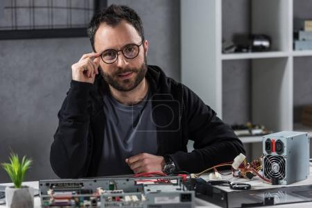 man with hand on glasses  looking at camera against computer details on table