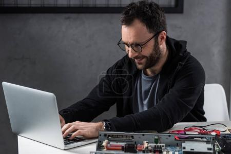 Photo for Smiling man using laptop against broken pc on table - Royalty Free Image