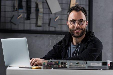 smiling man looking at camera while using laptop