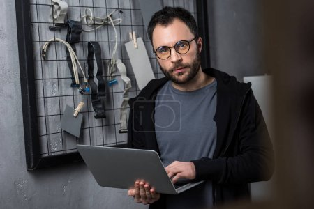 man holding laptop while looking at camera